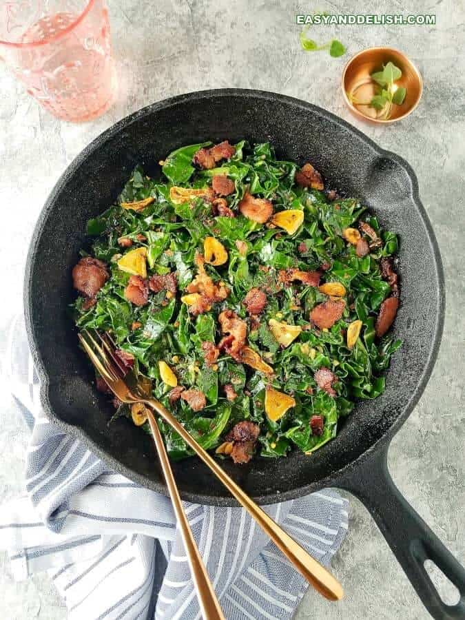 Brazilian garlicky collard greens with bacon in a skillet with garnish on the side (couve a mineira com bacom)