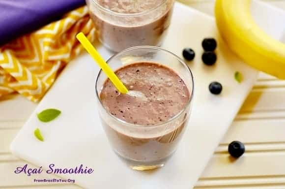 acai smoothie in a glass with fruits on the side