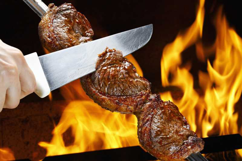 grilled rump cover or culotte steak in long metal skewer close to open flames