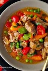 A bowl of Brazilian beef stew or picadinho with red tomatoes, green peas and cilantro, and orange carrots