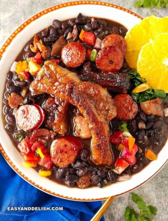 Bowl of feijoada black bean stew with pork sausage, pork ribs, oranges and collard greens