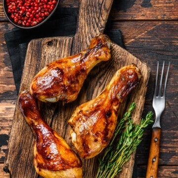 grilled chicken drumsticks over a cutting board with herbs