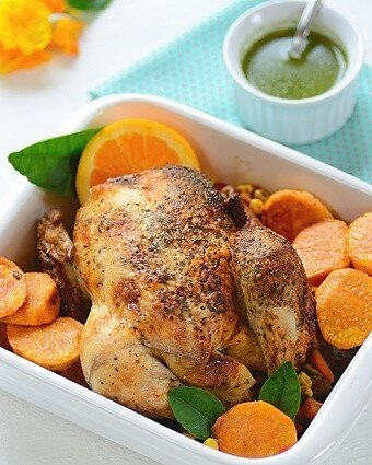 A baking dish with roast chicken with veggies and a bowl of chimichurri on the side