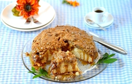 A plate with apple streusel cake partially sliced and a cup of coffee on the background