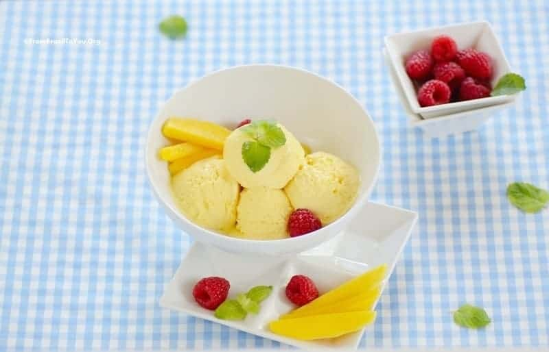 Mango Ice Cream in a bowl with garnishes on topa nd on the sides