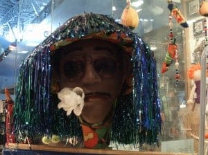 A statue of a person standing in front of a store display for Carnival