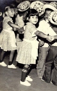 A vintage photo of a group of children dancing and posing for the camera