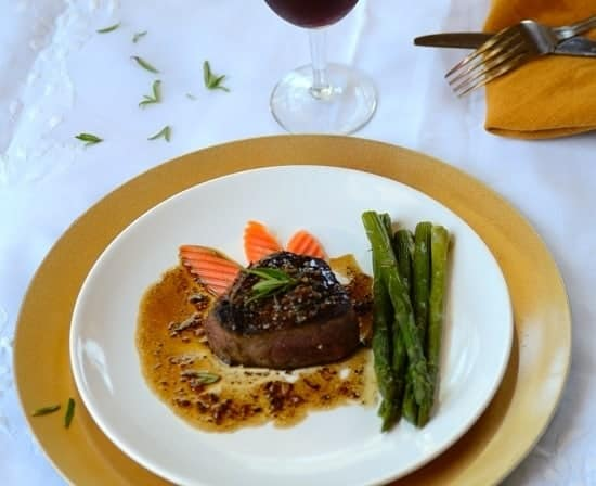 A plate with filet mignon with veggies and garnishes on the sides