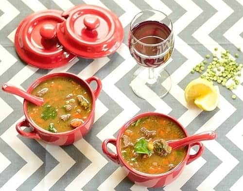 Lentil and Beef Soup served in bowls with a glass of wine on the side