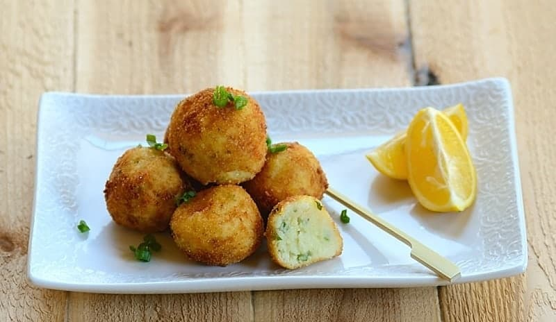A stack of fried, golden-brown breaded codfish balls on a plate with a garnish of lemon slices