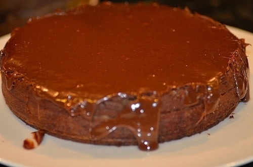A close up of a chocolate cake on a plate (Nega Maluca) topped with chocolate frosting