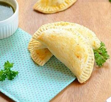 pizza empanadas on a table with sauce on the side