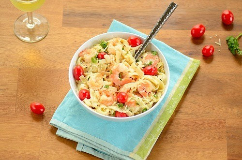 A bowl of pasta with shrimp and tomatoes