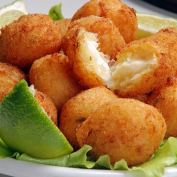 a bunch of cod cakes in a tray with lime wedges
