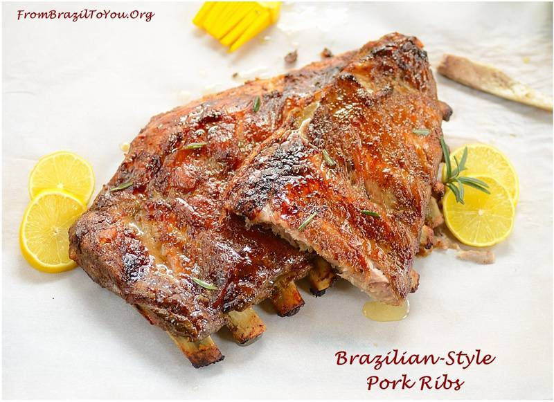 A rack of grilled Brazilian Style Pork ribs with wedges of lemon