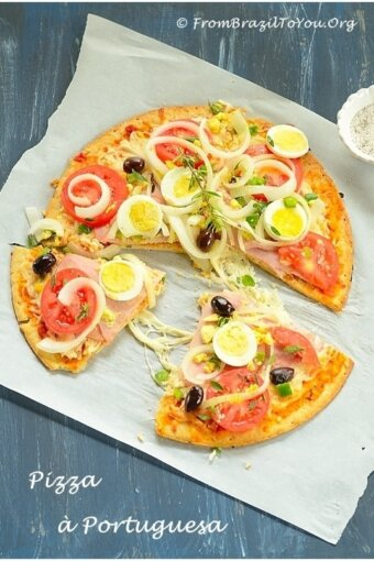 A whole sliced Pizza a portuguesa, topped with hard-boiled eggs, onions, tomatoes, green bell peppers, and black olives