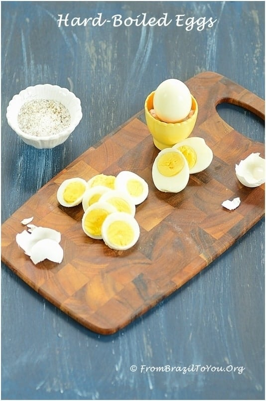 peeled, hard-boiled eggs on a board with salt on the side.