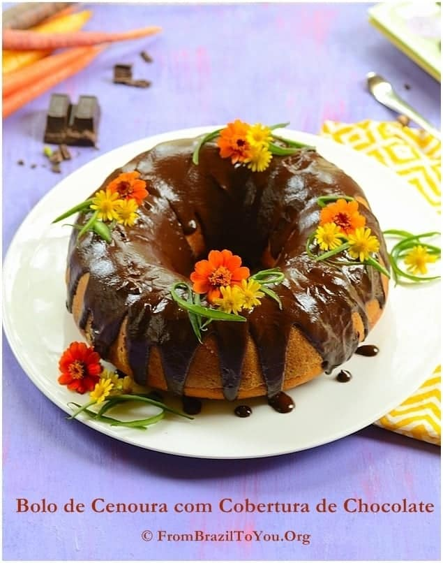 Carrot Cake topped with chocolate sauce and garnished with edible flowers on top