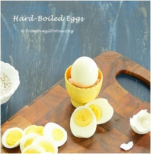 hard boiled eggs on a cutting board, one whole and others sliced