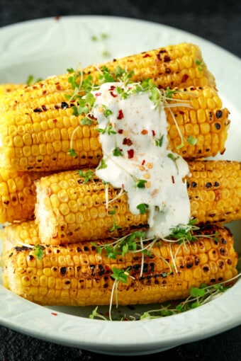 a pile of grilled corn on the cob with sauce on top
