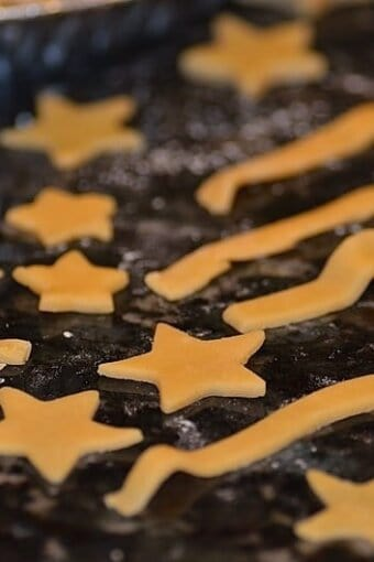 Pie dough cut into the shapes of stars and stripes resting on a floured surface