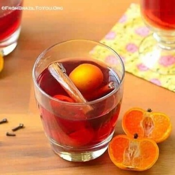 A glass of Brazilian mulled wine with orange halves on the side