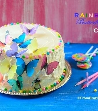 Rainbow cake sitting on top of a table and garnishes on the side to celebrate a birthday