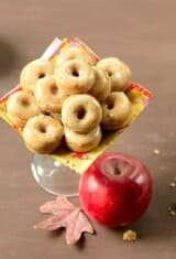 mini baked donuts in a platter with an apple on the side