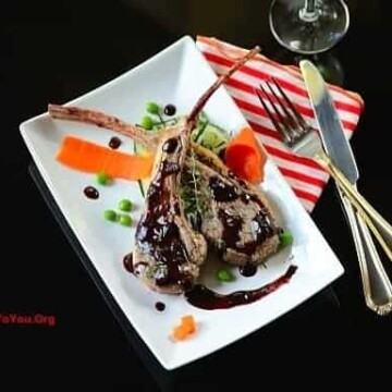 A plate of lamb chops with garnishes