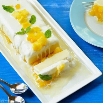 A plate of frozen pineapple trifle with spoons of the side
