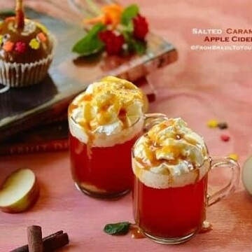 mugs of apple cider with garnishes on the sides