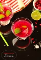 glasses of pomegranate caipirinha on a table with garnishes on the sides