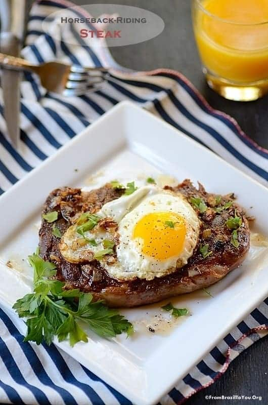 Grilled steak on a white plate, with a fried egg on top.