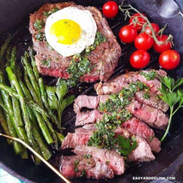 A skillet with steak and eggs plus vegetables (close up)