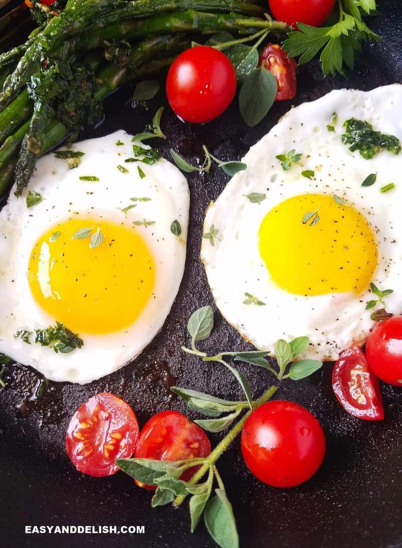 two eggs in a skillet with vegetables