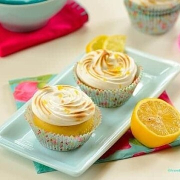 lemon meringue cupcakes in a platter with garnishes on the side