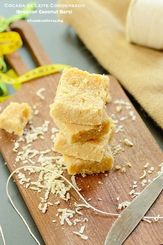 Stack of cocada de Leite condensado or sweet coconut bars on a wooden cutting board