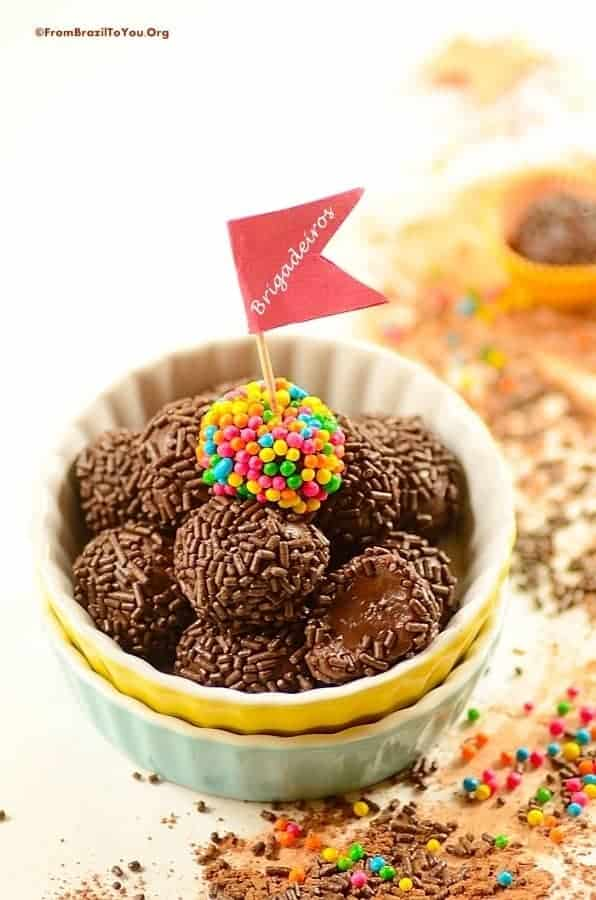 A bowl full of brigadeiro balls with a flag that says brigadeiros