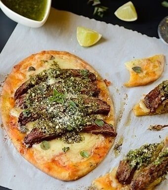 one meat flatbread on a table with some flatbread slices and garnishes on the sides