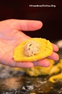A disc of coxinha dough held in the palm of the hand, with chicken filling in the center