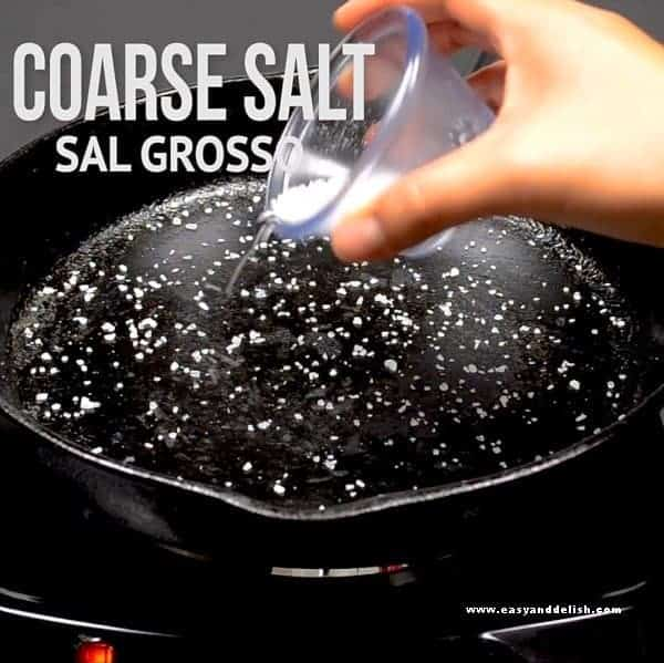 placing coarse salt in a pan to cook skirt steak