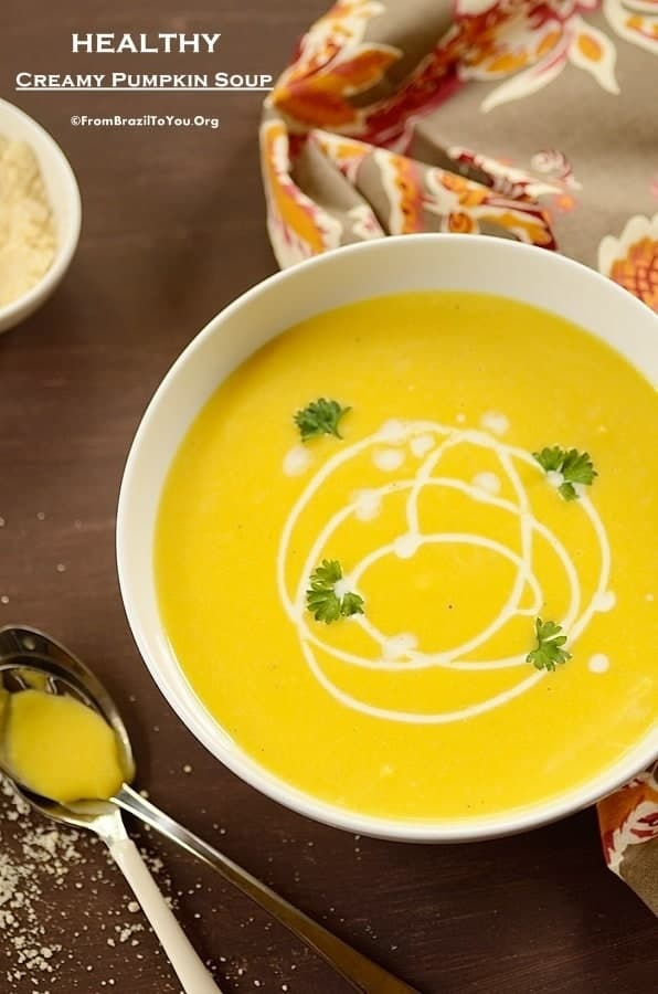 a bowl of creamy pumpkin soup drizzled with heavy cream and spoons on the side
