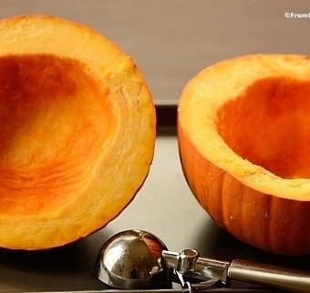 Two sliced pumpkin halves with their centers scooped clean with an ice cream scoop