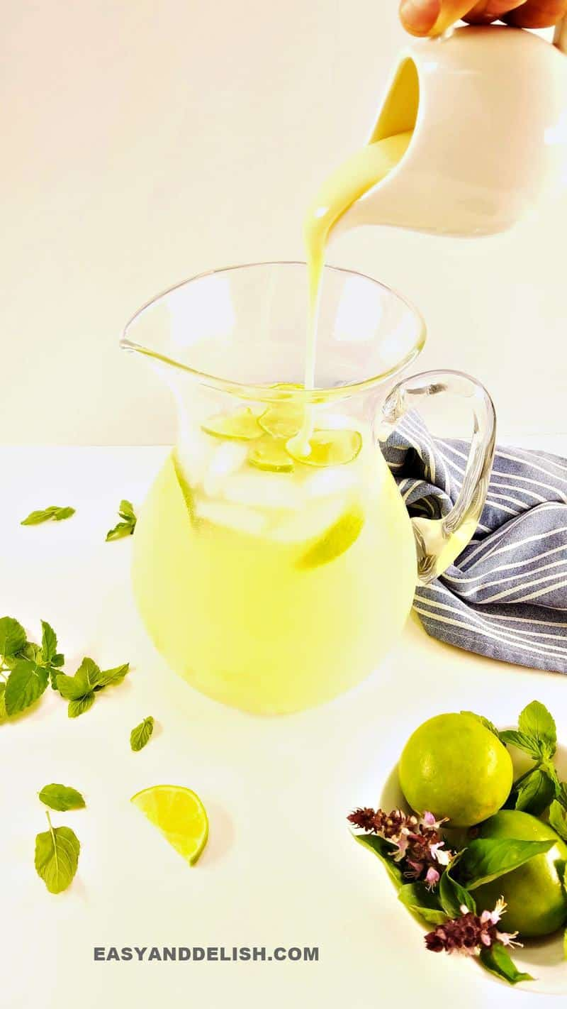 pouring condensed milk into a pitcher with lemonade