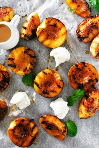 grilled peaches with ice cream and mint leaves