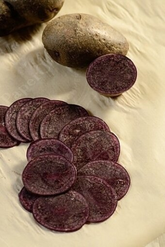 Many round slices of purple potatoes on a sheet of wax paper