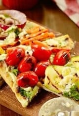 grilled vegetable pizza on a wooden board with a pizza cutter