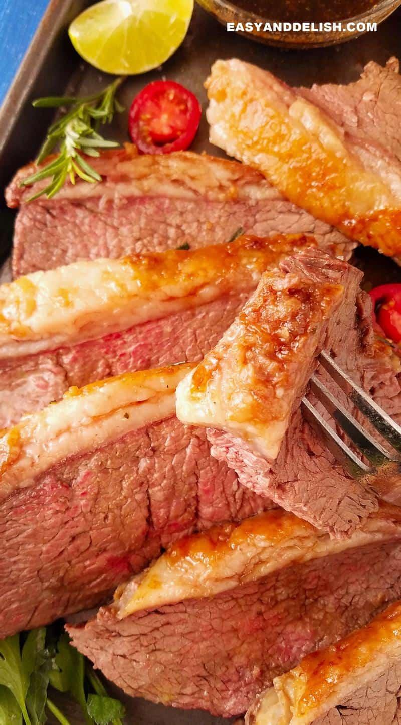 um pedaço do bife em um garfo mostrando a camada de gordura crocante