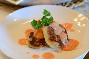 um prato com bolinhos de batata e molho rosé