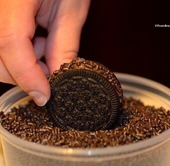 brigadeiro cookies being dredged in a container of chocolate sprinkles
